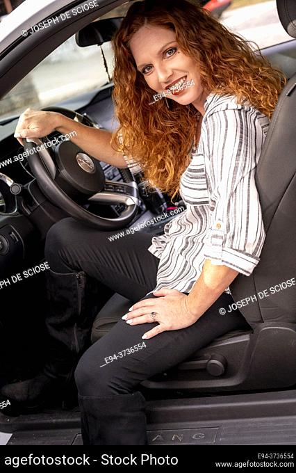 A beautiful 41 year old redheaded woman, looking at the camera in the driver's seat of a car