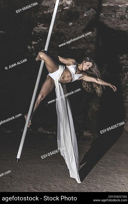 Young woman practices pole dance air in the cave interior