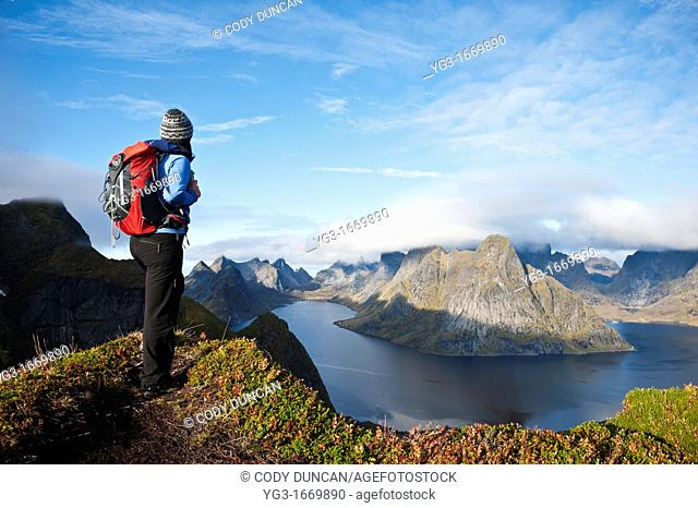 Female hiker enjoys spectacular view over mountains and fjords from Reinebringen, Lofoten islands, Norway