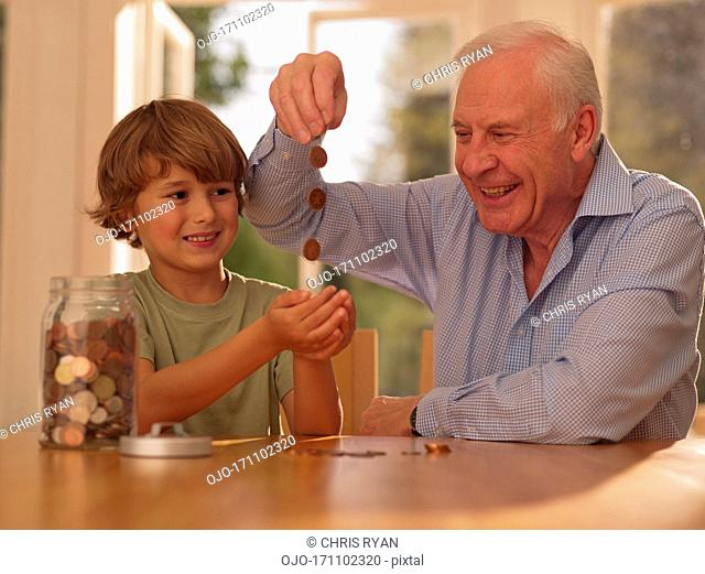 Grandfather and grandson with jar of coins