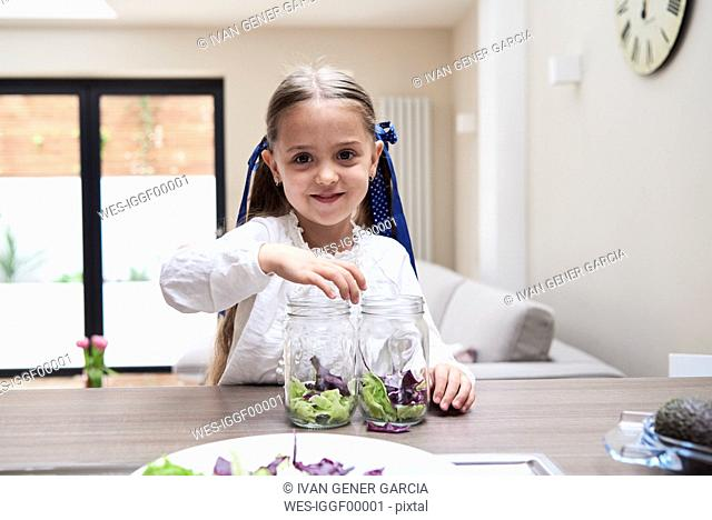 Portrait of little girl helping in the kitchen