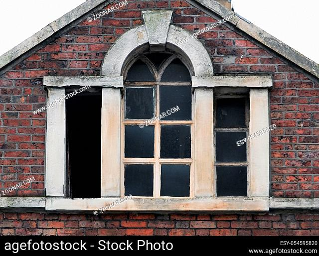 broken windows in an abandoned derelict old commercial building with brickwork stone frame and roof, Halifax england