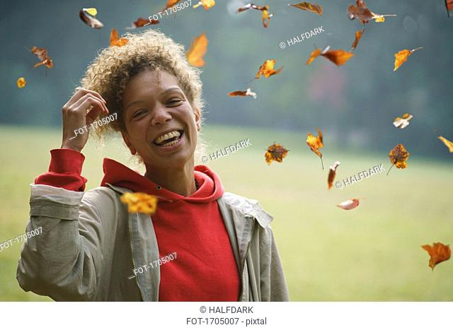 Portrait of cheerful woman with hand in hair amidst autumn leaves