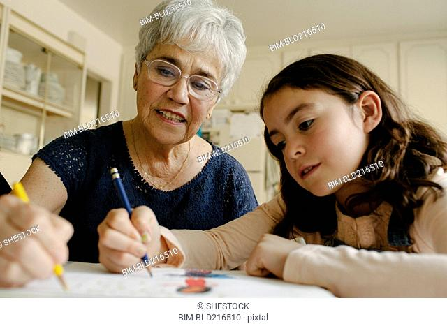 Grandmother and granddaughter drawing at table