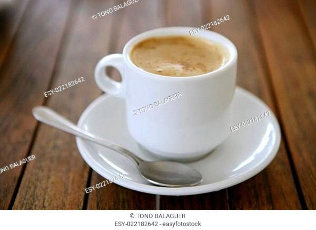 Coffe with milk white cup over teak wooden