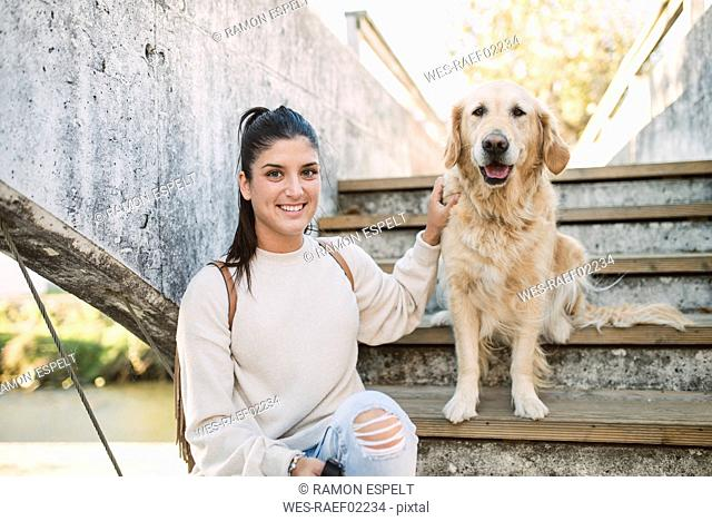 Portrait of a smiling young woman with her Golden retriever dog on stairs outdoors