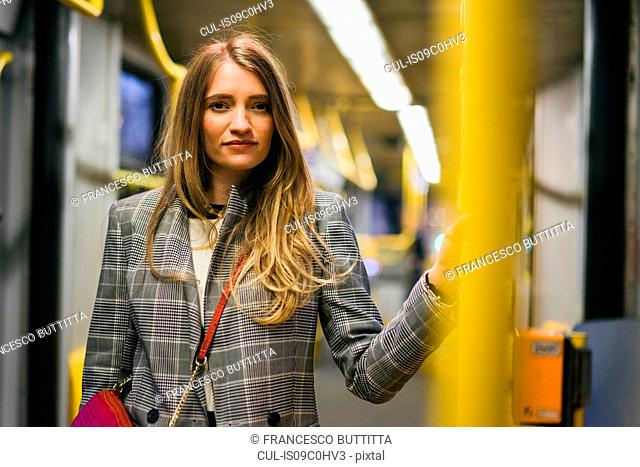 Young woman with long blond hair standing in train carriage, portrait