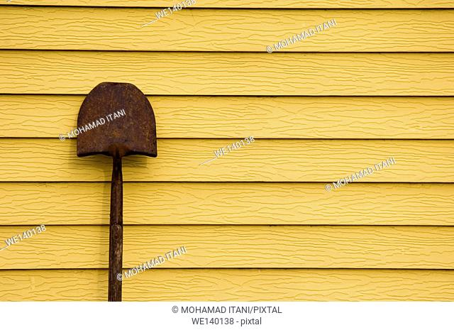 Rusty shovel against the wall