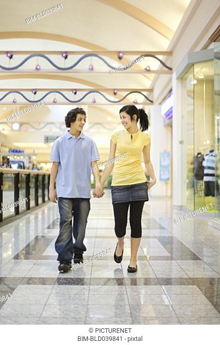 Multi-ethnic teenage couple holding hands in mall