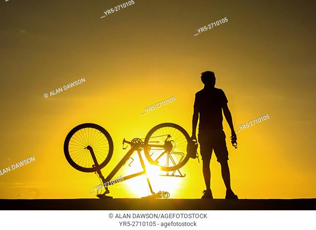 A mountain biker watches the sun rise over the Atlantic ocean from sea wall. Avenida Maritima, Las Palmas, Gran Canaria, Canary Islands, Spain. Europe
