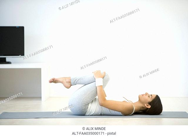 Woman lying on back, pulling knees up toward chest