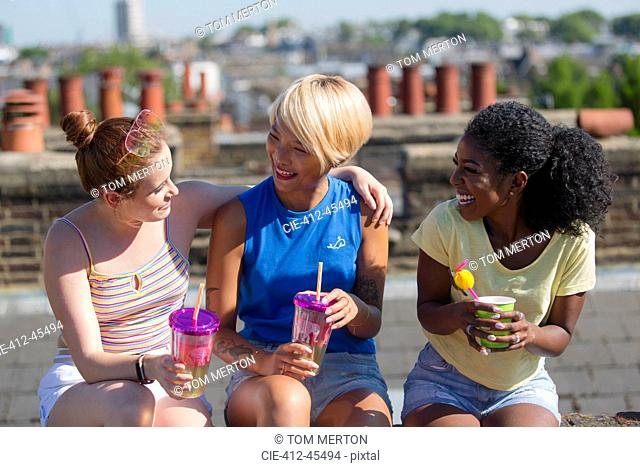 Young women friends bonding, drinking on sunny summer rooftop