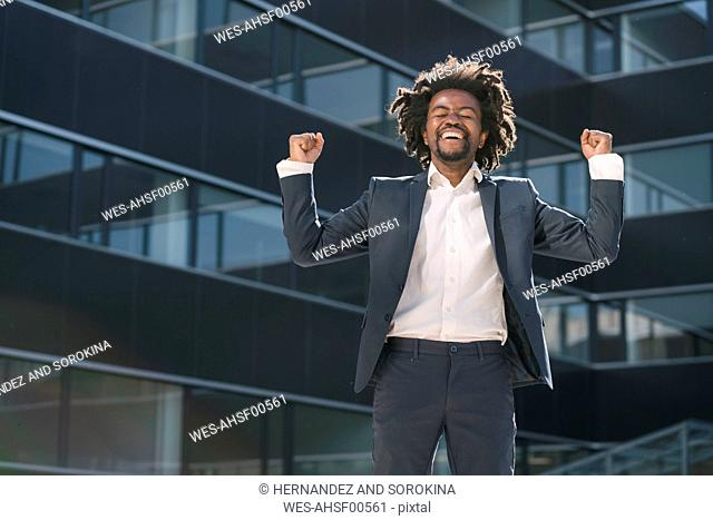 Excited businessman cheering outside office