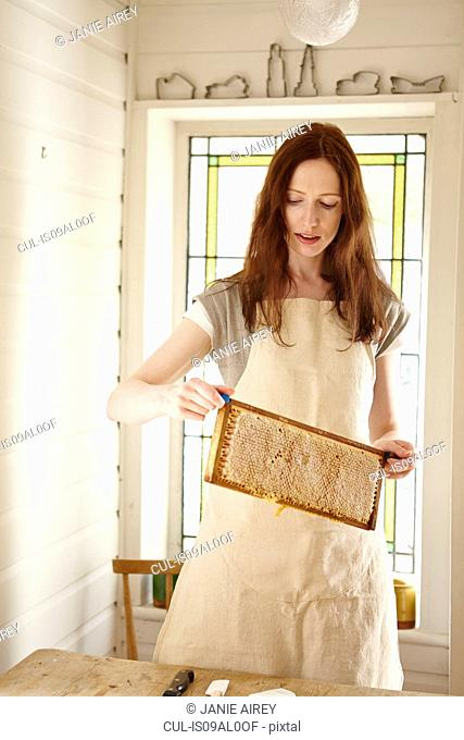 Female beekeeper in kitchen holding up super from beehive (honeycomb tray)