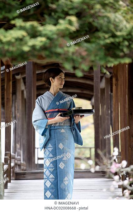 Young Japanese woman in kimono with tray walking on wooden bridge