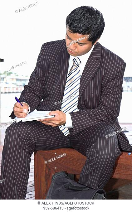 Young businessman writing on papers while working outside of the office