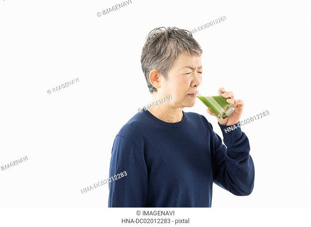 Senior woman drinking green smoothie