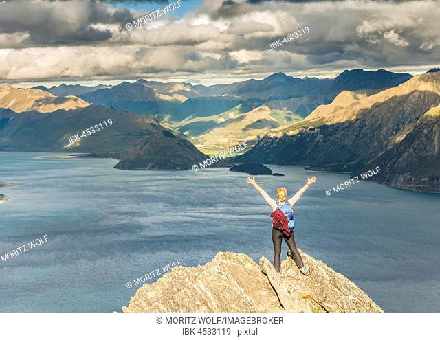 Female hiker on a rock, stretching arms in the air, Lake Hawea and mountain landscape, Isthmus Peak, Otago, South Island, New Zealand
