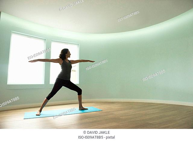 Mature woman practicing yoga in curved room