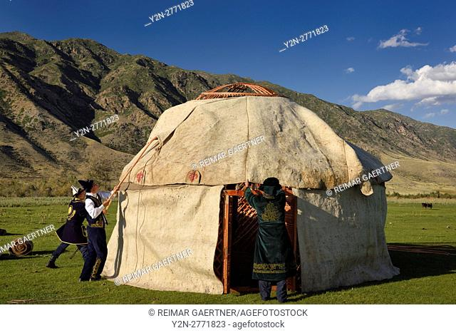 Men in traditional dress fit wool felt covers over Yurt roof frame in Saty Kazakhstan