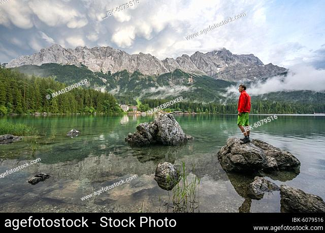 Young man standing on a rock on the shore, Eibsee lake in front of Zugspitze massif with Zugspitze, dramatic Mammaten clouds, Wetterstein range, near Grainau