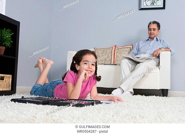 Father with newspaper and daughter doing homework on the carpet