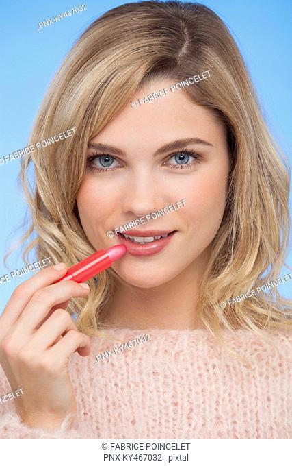 Woman applying lipstick on her lips