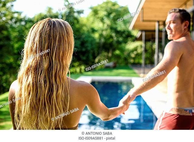 Mid adult man holding girlfriends hand at holiday apartment swimming pool