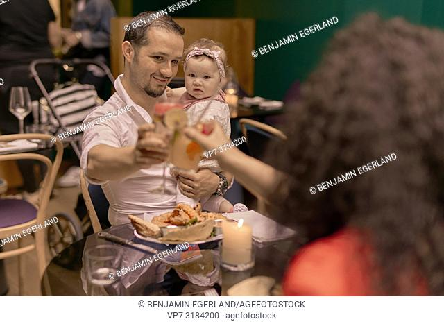 father with baby, chinking glasses, family eating in restaurant, Vegan Oriental, Kismet, in Munich, Germany