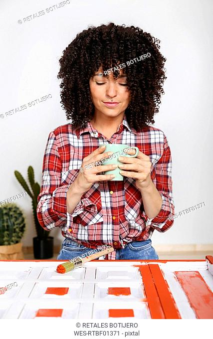 Woman holding cup of coffee at home, painted furniture