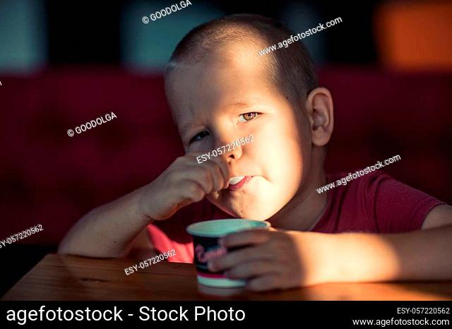 Portrait of a boy eating ice cream. High contrast hard light portrait
