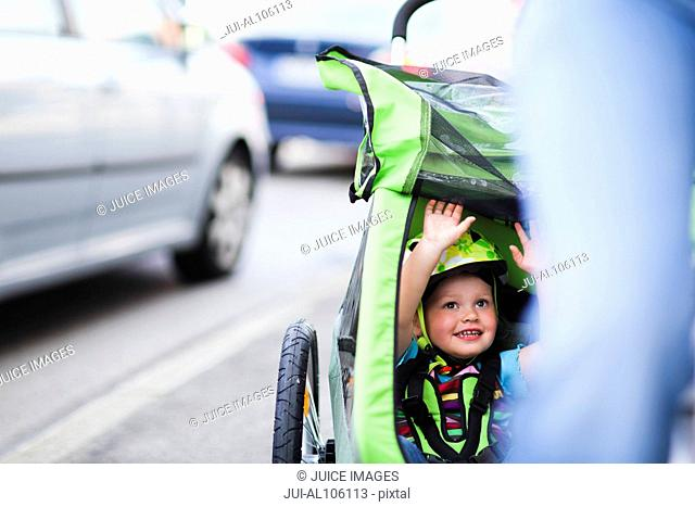 Young girl riding in stroller behind mother's bicycle