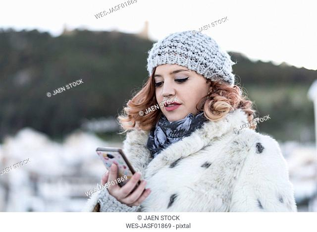 Portrait of young woman looking at cell phone in winter