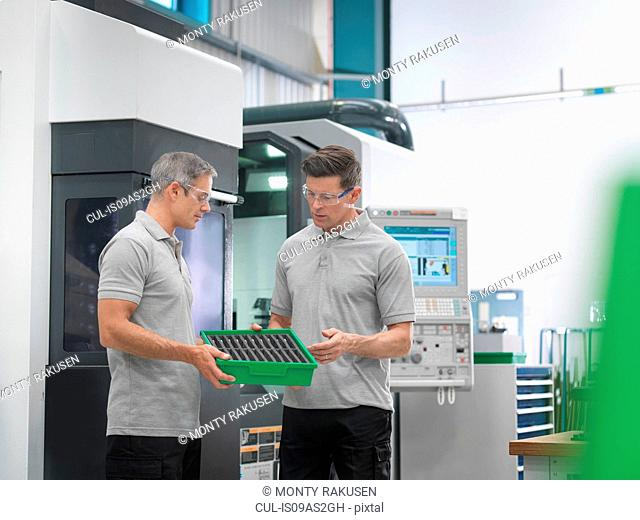 Engineers discussing machined products in orthopaedic factory
