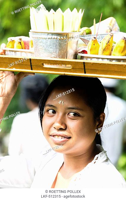 Young woman carrying tray with offerings on her head, Odalan temple festival, Munduk, Bali, Indonesia