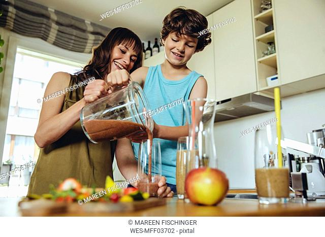 Mother and son pouring smoothie into glass