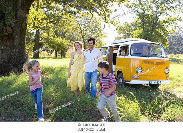 Family of four in field by camper van, son and daughter running 5-9, smiling