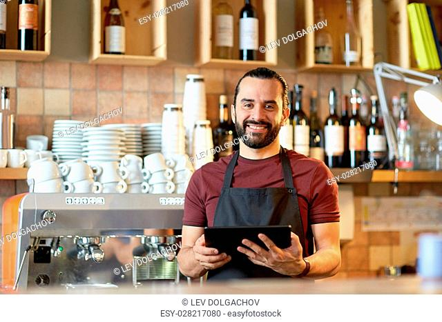 small business, people, technology and service concept - happy man or waiter in apron with tablet pc computer at bar or coffee shop