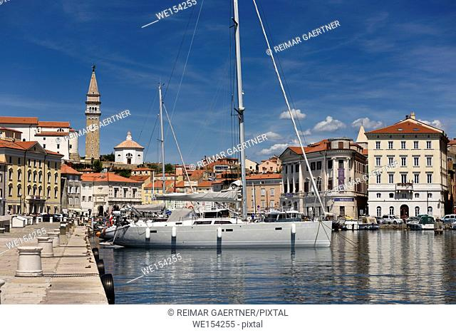 Yachts and boats in the inner harbor of Piran Slovenia with Cathedral, belfry and baptistery of St George's church