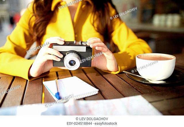 travel, tourism, photography, leisure and people concept - close up of young tourist woman or teenage girl with film camera and guidebook drinking cocoa at city...