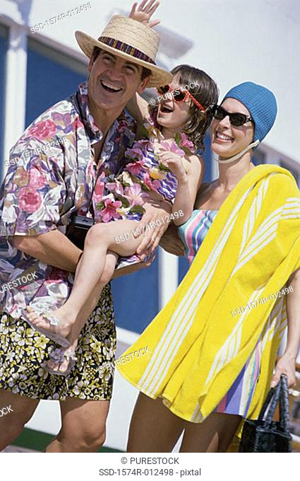 Mid adult couple with their daughter standing on a cruise ship smiling