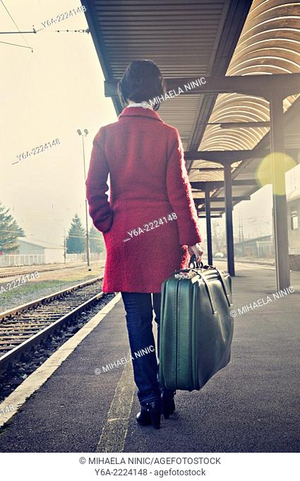 Woman carrying suitcase standing on railroad station platform, rear view