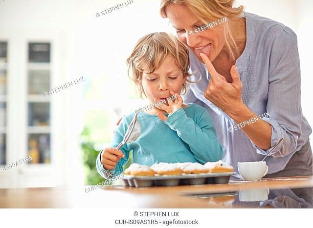 Mother and son making cupcakes in kitchen