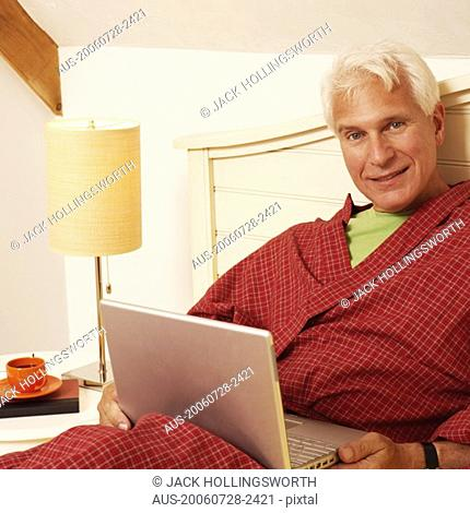 Portrait of a mature man leaning on the bed with a laptop