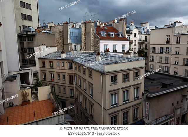 Rooftops in Paris with dark clouds