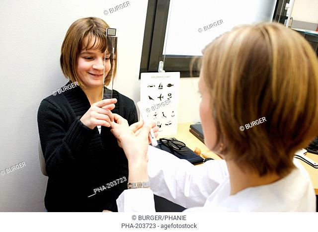 Teenage girl undergoing orthoptic check-up with an orthoptist. Department of Pediatric Ophthalmology, Limoges hospital, France