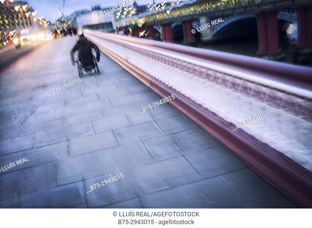 Unrecognizable man on wheelchair, crossing a bridge. Blackfriars, City of London, England
