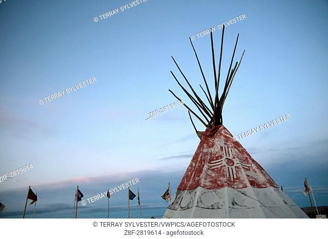 A tipi and tribal flags catch the evening light in the opposition camp against the Dakota Access oil pipeline on October 4, 2016