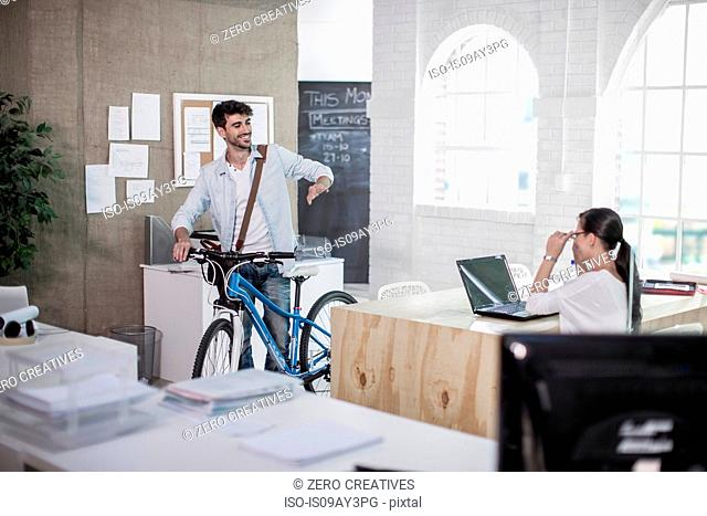 Male designer leaving work with bicycle in design studio