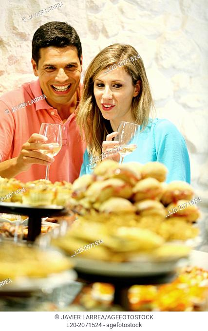 Couple drinking wine and eating tapas. Pintxos. Bar txondorra. Parte Vieja. Old town. San Sebastian. Donostia. Gipuzkoa. Basque Country. Spain